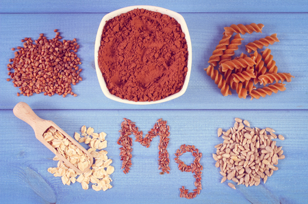 powdery: Vintage photo, Inscription Mg, ingredients and products containing magnesium and dietary fiber, healthy nutrition, wholemeal pasta, powdery cocoa, buckwheat, oatmeal, linseed, sunflower