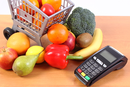 cashless: Payment terminal, credit card reader and fresh fruits and vegetables with plastic shopping carts, cashless paying for shopping, finance concept