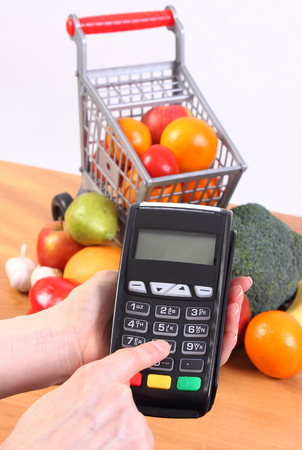 cashless: Hand of woman using payment terminal, enter personal identification number, credit card reader and fresh fruits and vegetables with plastic shopping carts, cashless paying for shopping