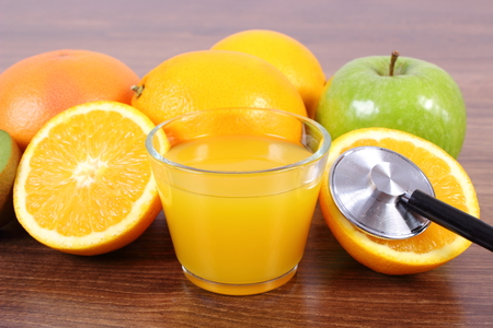 inmunidad: Medical stethoscope, fresh ripe fruits and glass of juice on wooden surface plank, grapefruit orange apple, healthy lifestyles nutrition and strengthening immunity Foto de archivo