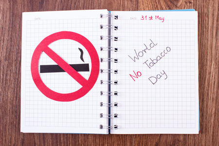 interdiction: Red no smoking sign made of paper and inscription world no tobacco day written in notebook, symbol of prohibited smoking, healthy lifestyle without cigarettes Stock Photo