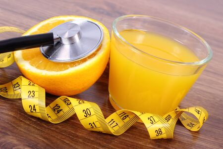 strengthening: Medical stethoscope, fresh ripe orange, glass of juice and tape measure on wooden surface plank, healthy lifestyles nutrition and strengthening immunity Stock Photo