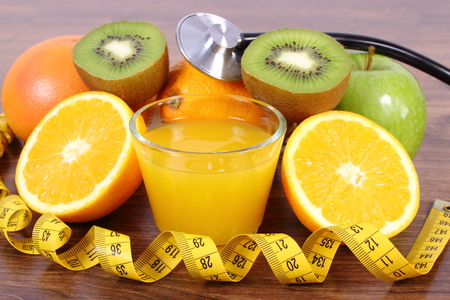 strengthening: Medical stethoscope and tape measure with fresh ripe fruits and glass of juice on wooden surface plank, grapefruit orange kiwi apple, healthy lifestyles nutrition and strengthening immunity