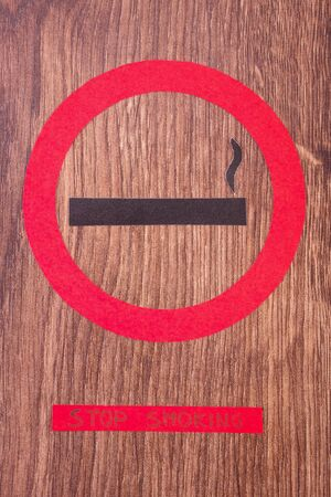 pernicious habit: Red no smoking sign made of paper with inscription stop smoking, symbol of prohibited smoking, healthy lifestyle without cigarettes Stock Photo