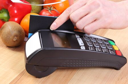 cashless: Using credit card reader, payment terminal with credit card and fresh fruits and vegetables, cashless paying for shopping Stock Photo