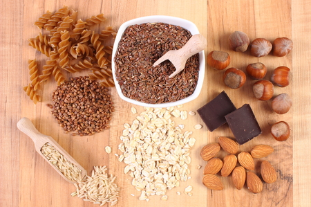 dietary fiber: Fresh, natural ingredients and products containing magnesium and dietary fiber, healthy food and nutrition, wholemeal pasta, buckwheat, brown rice, linseed, oatmeal, almonds, chocolate, hazelnut Stock Photo