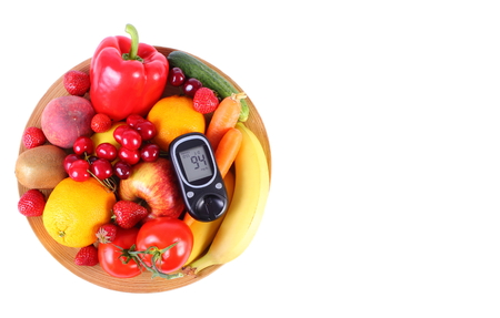 inmunidad: Glucose meter with fresh ripe fruits and vegetables lying on wooden plate, copy space for text, concept of diabetes, healthy food, nutrition and strengthening immunity. White background