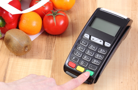 cashless: Using payment terminal, enter personal identification number, credit card reader and fruits and vegetables in paper shopping bag, cashless paying for shopping