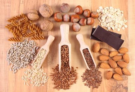 ingredienti freschi e naturali e di prodotti contenenti magnesio e fibra alimentare, cibo sano e la nutrizione, pasta integrale, semi di girasole, grano saraceno, riso integrale, semi di lino, mandorle, cioccolato, farina d'avena, nocciole, noci Archivio Fotografico