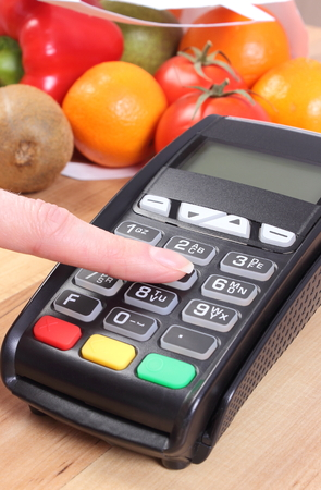 cashless: Using payment terminal, enter personal identification number, credit card reader and fruits and vegetables, cashless paying for shopping Stock Photo