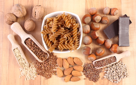 fiber food: Fresh, natural ingredients and products containing magnesium and dietary fiber, healthy food and nutrition, wholemeal pasta, buckwheat, brown rice, linseed, sunflower, almonds, hazelnut, walnut, chocolate