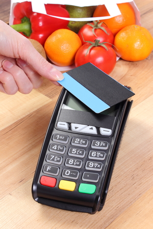 cashless: Using credit card reader, payment terminal with contactless credit card and fresh fruits and vegetables in paper shopping bag, cashless paying for shopping