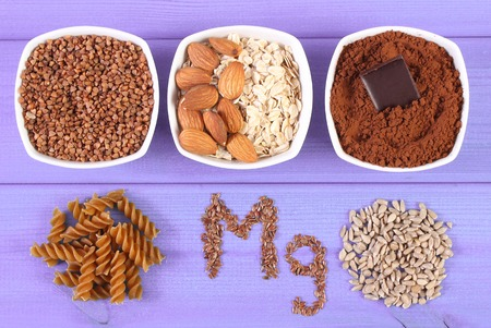 powdery: Inscription Mg, ingredients and products containing magnesium and dietary fiber, healthy nutrition, wholemeal pasta, sunflower, buckwheat, oatmeal, linseed, almonds, chocolate, powdery cocoa