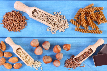 fiber food: Natural ingredients and products containing magnesium and dietary fiber, healthy food and nutrition, wholemeal pasta, sunflower, buckwheat, almonds, brown rice, hazelnut, linseed, chocolate