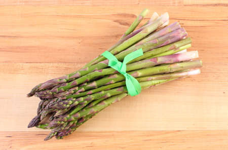 strengthening: Bunch of fresh green asparagus on wooden surface, concept of healthy food, nutrition and strengthening immunity Stock Photo