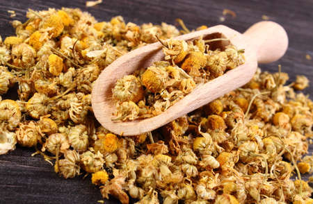herbalism: Heap of dried chamomile with wooden spoon lying on wooden surface, concept of healthy nutrition, herbalism and alternative medicine