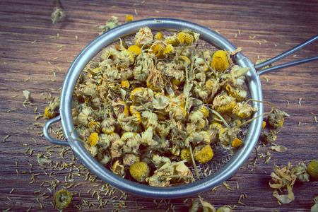 herbalism: Vintage photo, Heap of dried chamomile on metal sieve lying on wooden surface, concept of healthy nutrition, herbalism and alternative medicine