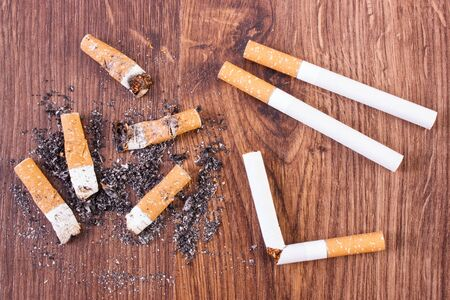 pernicious habit: Cigarette butts, ash and cigarette on wooden background