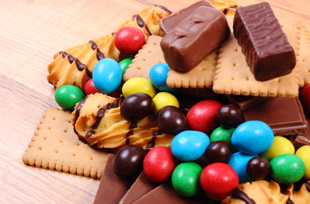 too many: Heap of candies and cookies on wooden table, too many sweets