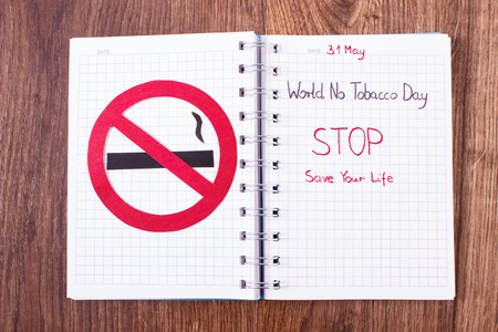pernicious habit: Red no smoking sign made of paper and inscription world no tobacco day written in notebook, symbol of prohibited smoking