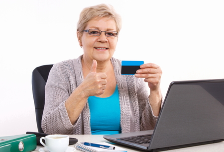 paying bills online: Senior woman, an elderly pensioner holding credit card and showing thumbs up, paying over internet for utility bills or online shopping, surfing internet Stock Photo