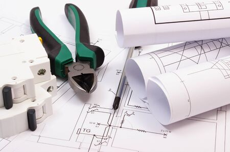 electrical equipment: Metal pliers, screwdriver, electric fuse and rolls of diagrams on construction drawing of house, work tool and drawing for projects engineer jobs