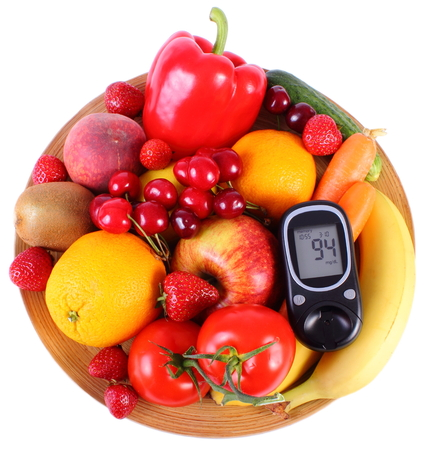 immunity: Glucose meter with fresh fruits and vegetables lying on wooden plate, concept of diabetes, healthy food, nutrition and strengthening immunity Stock Photo