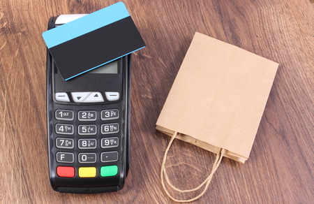 technology transaction: Credit card reader, payment terminal with credit card and paper shopping bag