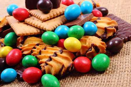 too many: Heap of candies and cookies on jute burlap, too many sweets