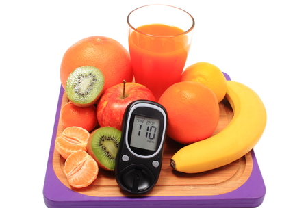 immunity: Glucose meter, fresh ripe natural fruits and glass of juice on cutting board, concept for diabetes, healthy nutrition and strengthening immunity