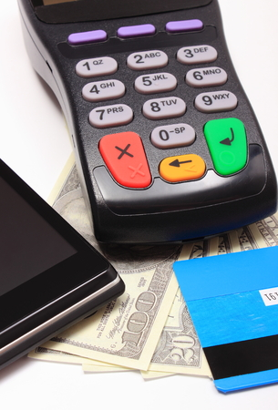 contactless: Payment terminal, contactless credit card and mobile phone with NFC technology and money, credit card reader, payment terminal with cash, finance concept Stock Photo