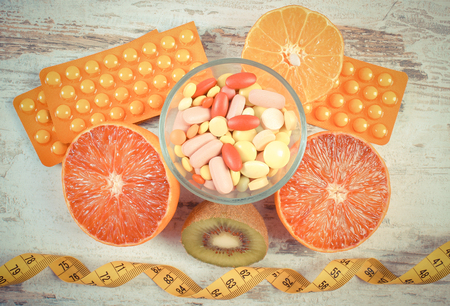 medical choice: Vintage photo, Fresh natural fruits, tape measure, medical pills, tablets and capsules, concept of slimming and choice between healthy nutrition and medical supplements