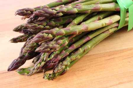 inmunidad: Bunch of fresh green asparagus on wooden surface, concept of healthy food, nutrition and strengthening immunity Foto de archivo
