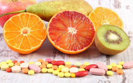 medical choice: Fresh natural fruits and pills, tablets or capsules, choice between healthy nutrition and medical supplements