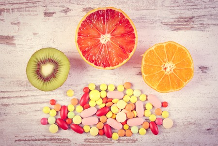 medical choice: Vintage photo, Fresh natural fruits and medical pills, tablets and capsules on rustic background, choice between healthy nutrition and medical supplements, healthy lifestyle