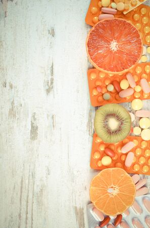medical choice: Vintage photo, Fresh natural fruits and pills, tablets or capsules, choice between healthy nutrition and medical supplements, copy space for text Stock Photo
