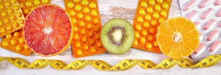 medical choice: Fresh fruits, tape measure and pills, tablets or capsules, concept of slimming and choice between healthy nutrition and medical supplements Stock Photo