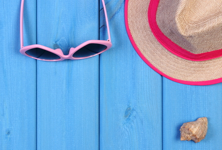 Pink sunglasses and straw hat with seashell on blue wooden boards, accessories for vacation and summer, copy space for text or inscription