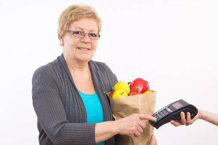 personal identification number: Elderly senior woman holding shopping bag with fruits and vegetables and using payment terminal, enter personal identification number, healthy nutrition in old age