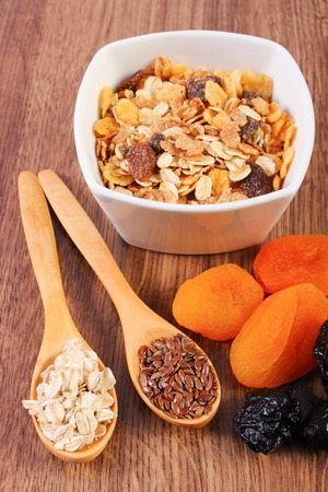 dietary fiber: Portion of linseed and rye flakes on spoon, dried fruits and muesli, concept of healthy nutrition and increase metabolism, ingredients with dietary fiber