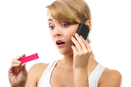 informing: Unhappy worried sad woman holding pregnancy test and talking on mobile phone, informing someone about positive result test, unwanted pregnancy