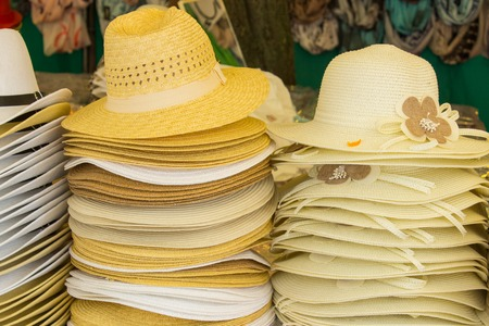 head protection: Collection of handmade straw hats on stall at the bazaar, summer fashion, head protection Stock Photo