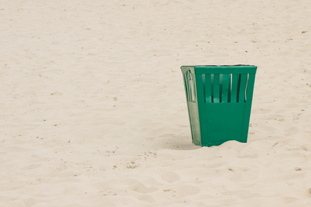 public waste: Empty old green trash can on sand at the beach, concept of environmental protection, littering of environmental, copy space for text