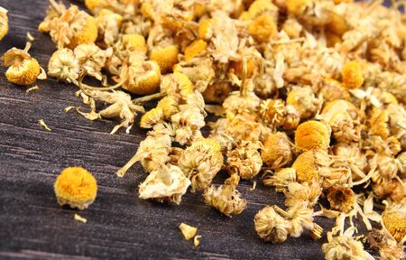 herbalism: Heap of dried chamomile lying on wooden surface, concept of healthy nutrition, herbalism and alternative medicine Stock Photo