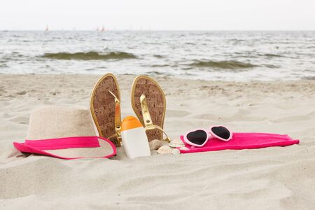 beach holiday: Accessories for vacation on sand at beach, sun protection on summer time, sunglasses, straw hat, sun lotion, sandals Stock Photo