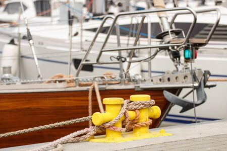 mooring bollard: Blue rope and yellow mooring bollard in port with yacht in background, detail of yachting Stock Photo