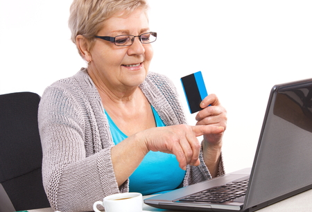 over paying: Senior woman, an elderly pensioner holding credit card and showing laptop screen, paying over internet for utility bills or online shopping, surfing internet Stock Photo