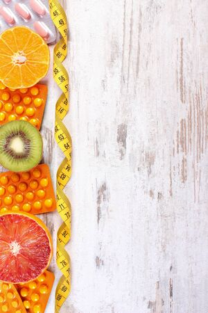 medical choice: Fresh fruits, tape measure and pills, tablets or capsules, concept of slimming and choice between healthy nutrition and medical supplements, copy space for text