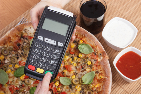 personal identification number: Using payment terminal, enter personal identification number, cashless paying for vegetarian pizza in restaurant, finance and banking concept