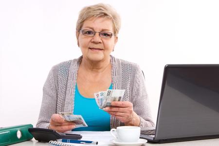 幸せな年配の女性、老後の保障の彼女のホーム、コンセプトで光熱費の通貨お金を数える高齢者の年金受給者
